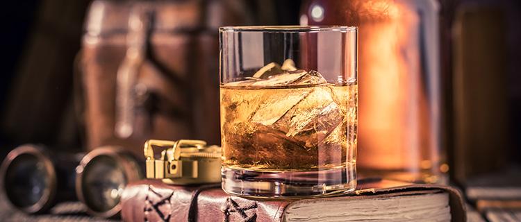 古い本の上に乗ったウイスキーグラス
